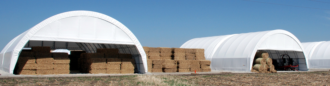 Three white hoop building open on the ends with bales of corn stover inside.