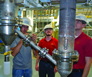 Three researchers inspecting the autothermal pyrolysis unit.