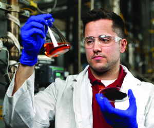 A researcher looking at products made from solvent liquefaction.